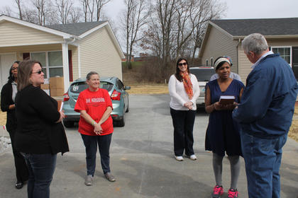Habitat for Humanity board member Rick Wagoner, right, presents a Bible to new homeowner Kimberly Phillips at the dedication of her home at 113 McGowan Ave. Her next-door neighbor, Sharon Bolin, at left, is the other new Habitat homeowner.
