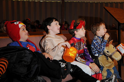 """Ty Sweazy, T.J. Karr, Justin Mobley and James Mobley watch """"It's the Great Pumpkin, Charlie Brown"""" during the harvest party at Nelson Christian Church Friday."""