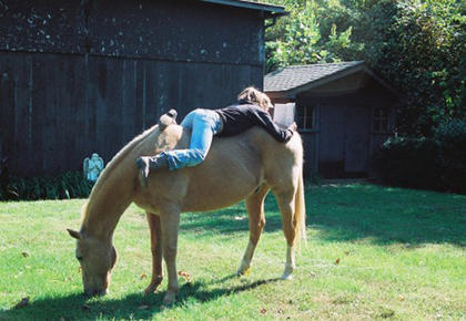 Taylor Duncan relaxing/reading on her horse Bo.   We can leave him out and he just hangs out like a dog, it's funny