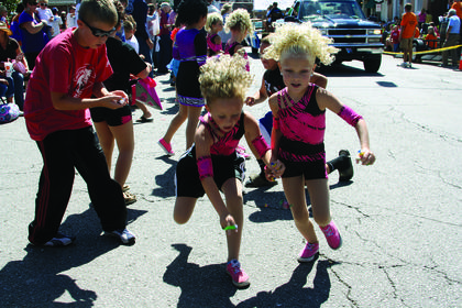 Two girls run to grab pieces of candy that were handed out during the Rolling Fork Iron Horse Festival parade. Several groups, such as the Thomas Nelson High School band and St. Catherine Academy, participated in the parade.