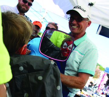 Mark Love, of Smiths Grove, holds a mirror for Anderson Clemons, 2, of Bardstown, to see his face after it is painted like Spiderman during the Iron Horse Festival.