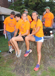 Jennifer Jackey and Skyler Ballard relax on an old tree stump outside Spalding Hall before the race.