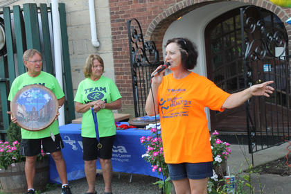 Jan Tronzo, director of the Nelson County Community Clinic, speaks at the awards ceremony of the free clinic's Run for the Health of It 5K Saturday. The event involved 198 runners and raised an estimated $26,000 including sponsorships. Leon and Margaret Claywell, left, are the owners of Medica Pharmacy, the presenting sponsor of the race for the second consecutive year.