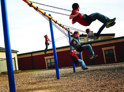 Children swing at the playground after school Monday, the warmest day of the year so far.