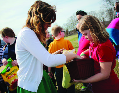 Science teacher Christina Jimison helps students plant cilantro and basil after school Monday.