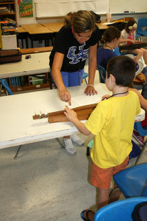 An assistant helps a young student during a dulcimer lesson at Kid's Camp.