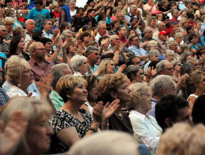 Audience members clap in rhythm during a performance by Lee Greenwood at the J. Dan Talbott Ampitheatre Saturday. The crowd was solid, with a few open seats in the upper areas of the audience.