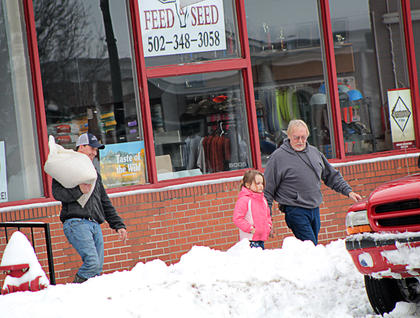 A family braves the snow to pick up items from a local feed store Thursday.