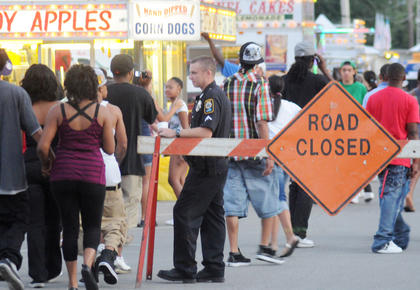 Mike Medley, Bardstown Police Department, monitors the activities at the Buttermilk Days Festival Friday night. The crowd swelled after the Nelson County High School game was over.