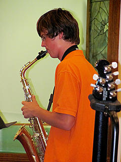 "Colin Brown plays ""Amazing Grace"" on the saxophone during the baptism event at Mill Creek Baptist Church Aug. 7."