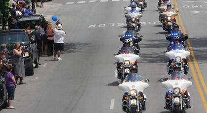 A phalanx of motorcycle police officers approaches the old courthourse from East Stephen Foster, as members of the community line the street for the procession.