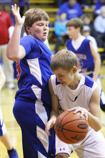 Jerry Wimsett (right) of New Haven drives around Bloomfield's Seth Hall in last week's seventh grade championship game. Wimsett led New Haven in scoring.