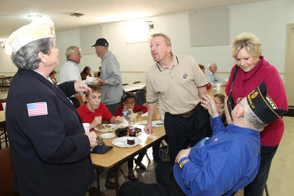 Lt. Col. Michael Muller, center, talks with Arlene L. daCorte of Bardstown, state commander of the Disabled American Veterans Auxiliary, while veteran Russell Marlowe, seated, talks with Rita Peake. Muller was the keynote speaker at the Bardstown Veterans Day event at Veterans Park on Broadway.