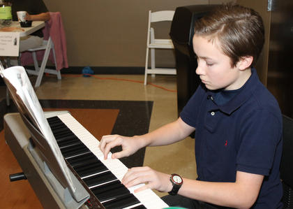 Noah Surtees provides the music to accompany the meal at the Souper Bowling of Caring at St. Joe's Parish Hall.