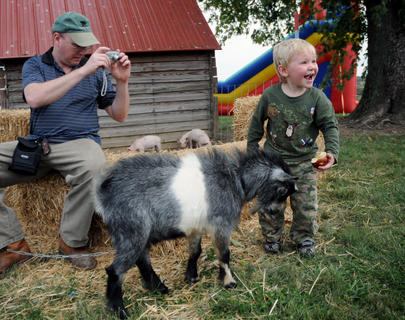 Tommy Cecil, Greenbriar, takes a photo of Colton Cecil, 3 years old, who pets a goat at Watson's Pumpkin Festival Sunday.