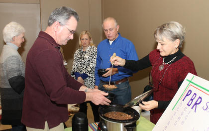 Lynne Bowling serves Sidney Hagan at the PBR Soup table. The recipe doesn't have any Pabst Blue Ribbon in it. The PBR stands for pheasant, beans and rice. All the money from donations goes to benefit the St. Vincent de Paul Society, which helps needy local residents.