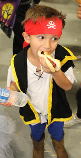 Javier Sanchez, 5, chows down on a hot-dog at the Guthrie Opportunity Center trick-or-treat party. He is the son of Martin Sanchez and Jennifer Rojas.