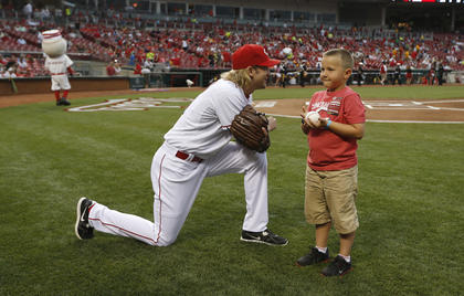 Cincinnati Reds starting pitcher Bronson Arroyo (61) talks with Parker Ellis, 6 son of slain Bardstown police officer Jason Ellis prior to throwing out the first pitch before their game against the Pittsburgh Pirates at Great American Ball Park. The Enquirer/Jeff Swinger