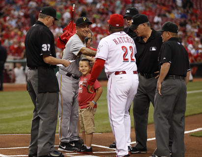 Parker Ellis, 6 son of slain Bardstown police officer Jason Ellis was alls miles as he took out the Cincinnati Reds lineup with first base coach Billy Hatcher after throwing out the ceremonial first pitch before their game against the Pittsburgh Pirates at Great American Ball Park. The Enquirer/Jeff Swinger