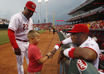 Cincinnati Reds first base coach Billy Hatcher introduces Parker Ellis, 6 son of slain Bardstown police officer Jason Ellis to manager Dusty Baker after throwing out the ceremonial first pitch before their game against the Pittsburgh Pirates at Great American Ball Park. The Enquirer/Jeff Swinger