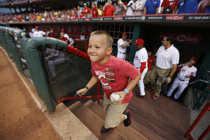 Parker Ellis, 6 son of slain Bardstown police officer Jason Ellis runs out of the Cincinnati Reds dugout after getting a ball. Parker threw out the ceremonial first pitch before their game against the Pittsburgh Pirates at Great American Ball Park. The Enquirer/Jeff Swinger