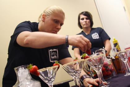 """Angie Leake, a bartender at the Old Talbott Tavern, places a strawberry onto a martini glass as fellow bartender, Heather Richards, stands nearby before the Kentucky Bourbon Festival Mixed Drink Challenge Wednesday. Leake's and Richards's drink, """"A Sidecar Named Desire,"""" was named the overall grand champion and will be the signature drink of the 2014 Kentucky Bourbon Festival."""