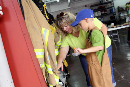 Krista Foster shows her 8-year-old son, Zachary, some firemen coats on display during the Safety Day Open House at the Bardstown Fire Department on N. 5th Street Saturday.