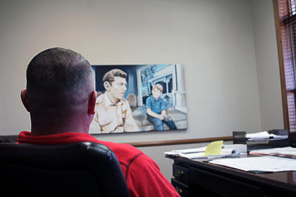 "Sheriff Ed Mattingly looks at a painting by local artist Bettye Brookfield, at the Nelson County Sheriff's Office. The painting, called ""A Sheriff's Wisdom and Protection,"" depicts beloved TV Sheriff Andy Taylor and his son Opie sitting on the porch of their home."
