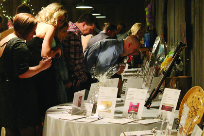 People browse items featured in the silent auction at Saturday's Boots & Bling event at the Blue Grass Entertainment and Exposition Complex.