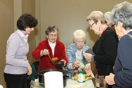 Sister Earline Hobbs ladels some chili into a bowl for a guest while Sister Ann Boone takes the money. At left is Mary Manion, a volunteer for the St. Vincent de Paul Society, who was helping the Sisters of Charity. The nuns were the winners of this year's chili competition at the Souper Bowl of Caring.