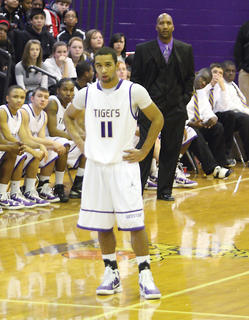 """Bardstown junior Jordan Brewer (11), his father, James """"Boo"""" Brewer (standing) and the Tiger bench watch during a free throw attempt."""