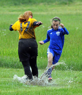 Mollie Bodkin of the Nelson Elite Smashers (right) battles the mud and an opponent during a recent game.