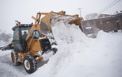 A city worker clears snow from the Bardstown public parking lot on Flaget Monday morning.
