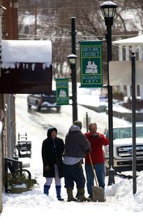 From right, Jack Morgan, TK Broaddus and Betty Adam work to clear snow from the sidewalk in downtown Bloomfield Monday afternoon.