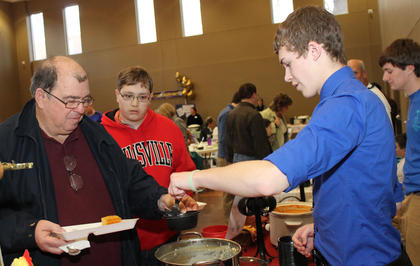 Brendan Mathews serves soup to Ed and Devin Gordon at the St. Joseph Catholic Church's Souper Bowl of Caring the day before the big game. Also working the Fowl Play chicken soup table is Mark Newcomb.