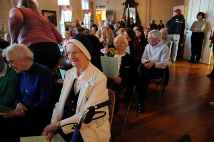 Sister Alice Theresa Wood, who lives at Nazareth, gathers with others at the unveiling of the Christmas stamp for 2011 at Nazareth Friday. This year's stamp depicts Madonna of the Candelabra by Raphael.