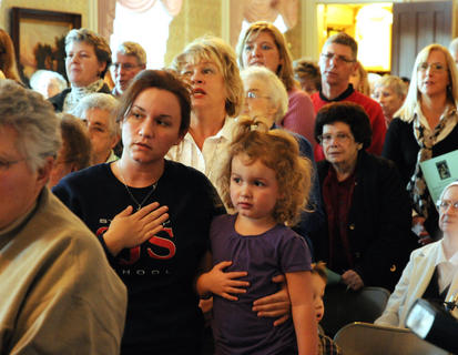 Crystal Logsdon and her daughter Abigail Logsdon place their hand over their hearts during the singing of The Star Spangled Banner during the unveiling of the Christmas stamp for 2011 at Nazareth Friday. The unveiling was the first to take place outside New York City. The Post office at Nazareth has been open since 1888 and remains open today.