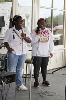 Aleah Graham, the Harvest Homecoming Queen, and her sister Devin Hunter sing for a small crowd Saturday afternoon.