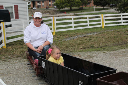 Kelsey Brook Milburn, 2, rides the train at the festival. She insisted her mother, Tracy Milburn, ride the train too.