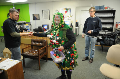 """A mysterious """"Christmas tree"""" visited Standard Communications offices the Friday before Christmas. The """"tree"""" presents an ornament to Chris Swarts while News Director Tom Isaac watches and waits. There were reports of the tree lady's visit all over town."""