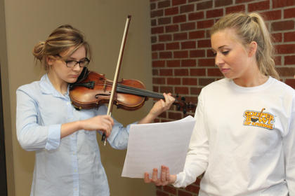 Kate Stiles plays the violin at the Souper Bowl of Caring while Marie Blevins holds the sheet music for her. Both are Bethlehem High School students.